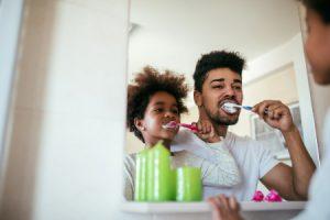 Man Brushing Child's Teeth